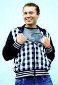 Gelukkig grappige jonge man glimlacht en opstijgt zijn jas — Stockfoto