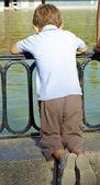 Niño mira al lago — Foto de Stock