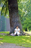 Woman reads near the tree — Stock Photo