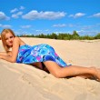 Half naked girl covered with a tissue poses on the sand — Photo