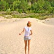 Sexual girl in shorts walks over the sand — Stok fotoğraf