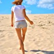 Sexual girl in shorts walks over the sand — Stock Photo