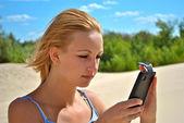 Girl checks her phone — Stock Photo