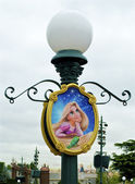 Lamp post with a picture of Sleeping beauty — Stock Photo