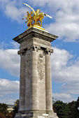 Column with a golden statue on the bridge of Alexandre III, Paris, France — Stock Photo