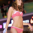 Brunette contestant girl dances in red and white bikini wearing black hat — Stock Photo #13709645