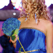 Beautiful blond contestant poses in blue dress and with blue flowers — Stock Photo #13709856