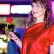 Brunette contestant in purpre dress with red rose — Stock Photo #13709899