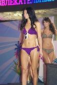Brunette girl poses in a violet bikini — Stock Photo