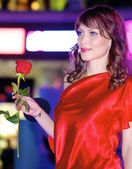 Brunette contestant in a purpre dress with red rose — Stock Photo