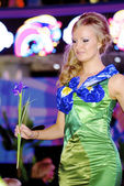 Amazing blonde contestant walks over the runway in a green dress — Stock Photo