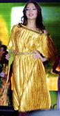 Brunett tävlande tjej i en gul klänning går — Stockfoto