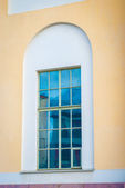 Window on the yellow wall in Saint Petersburg — Stock Photo