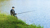 Man is fishing in the lake — Stock Photo