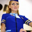 Girl in a stewardess costume poses at the Nikon stand - 图库照片