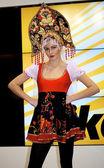 Beautiful girl poses in Russian costume supporting NIKON — Stock Photo