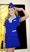 Girl in a stewardess costume poses at the Nikon stand — Stock Photo