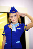 Beautiful girl wears the stewardess costume at the Nikon stand — Stock Photo