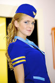 Beautiful girl in a stewardess costume at the Nikon stand — Stock Photo