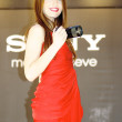Girl in a red dress promotes the SONY camera — Stock Photo