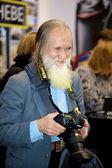Sympathic old man takes photos — Stock Photo