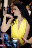 Dziewczyna w żółtej sukience działa na stoisku nikon — Zdjęcie stockowe