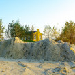 Stock Photo: Small yellow huose behind sand mountain