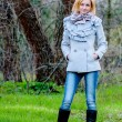 Stock Photo: Beautiful girl poses in forest wearing coat and jeans
