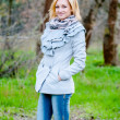 Beautiful blond caucasian model poses in grey coat, jeans and black boots — Stock Photo #14704337