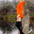 Stock Photo: Blond girl poses in orange dress in forest