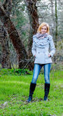 красивая девушка позирует в лесу, носить пальто и джинсы — Стоковое фото
