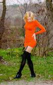 Blond girl poses in an orange dress in the forest — Stock Photo