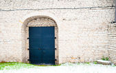 Black door of the stone wall — Stock Photo