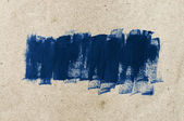 Blue hand-painted brush stroke daub over old vintage paper — Stock Photo