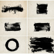 A set of black hand painted black daubs and brush strokes over old vintage paper - canvas — Stock Photo