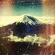 Distressed vintage grungy photo of Cotopaxi volcano (Ecuador) seen from an airplane — Stock Photo #34555109