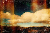 Distressed vintage grungy photo of clouds and mountains — Stock fotografie