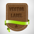 Vector vintage leather badge with green silky ribbon — Stock Vector