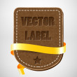 Vector vintage leather badge with yellow silky ribbon — Stock Vector