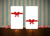 Vector white paper cards with festive silky ribbon bow knots over an old wall background with vintage wallpaper — Vector de stock