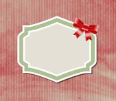 Vintage label tag with satin ribbon bow knot over old paper background — Stok Vektör