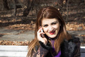 Young girl in a park talking on phone — Stockfoto