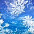 Stock Photo: Wintery Holiday Snowflakes Against Blue Background