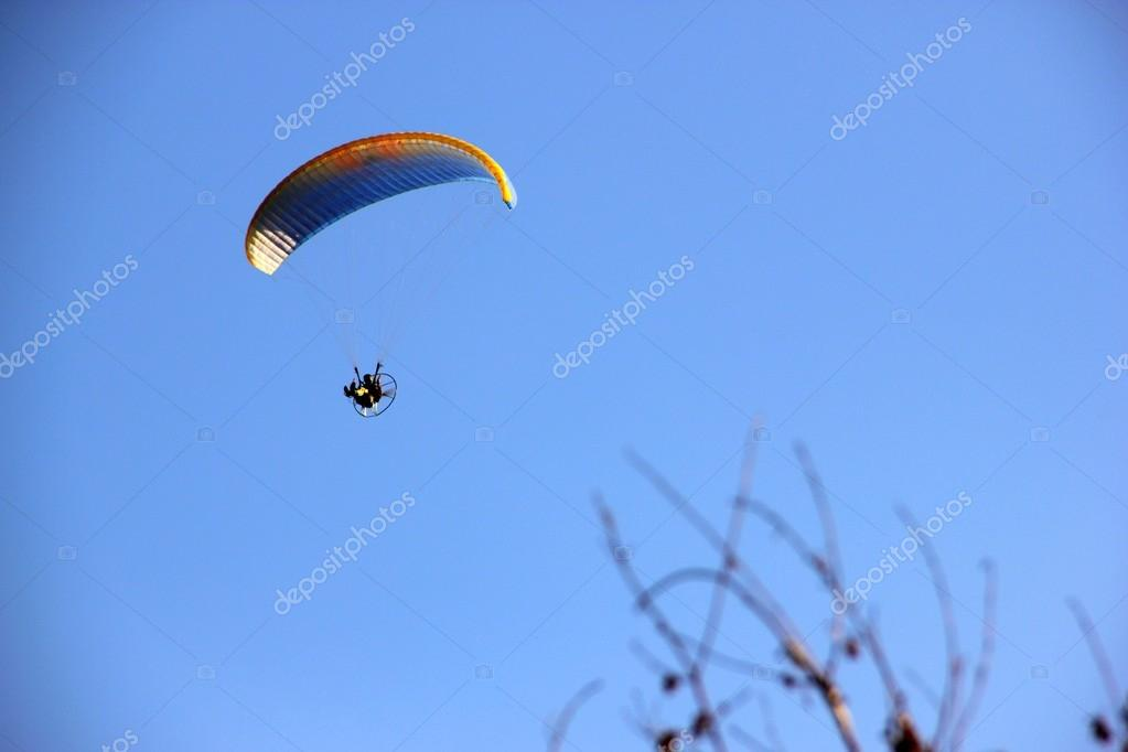 Yellow and blue powered paragliding with sky background — Stock Photo #12865534