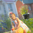 Smiling girl with apple on pumpking at garden - harvesting time — Stock Photo #32023625