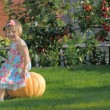 Smiling girl on pumpking over apple tree on a farm — Stock Photo