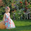 Smiling girl on pumpking over apple tree on farm — Stock Photo #32023631