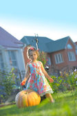 Serious girl with apple at pumpking in garden - harvesting time — Stock Photo