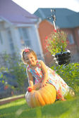 Smiling girl with apple on pumpking at garden - harvesting time — Stock Photo