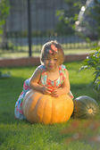 Smiling girl on pumpking on a farm — Stock Photo